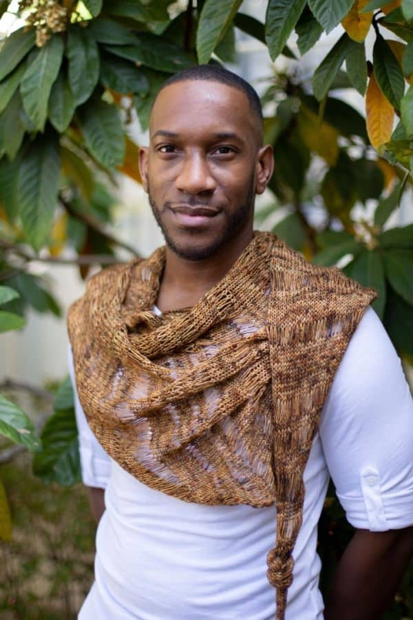 Black man in a white tee shirt wearing a brown and rust-toned shawl in front of a background of greenery