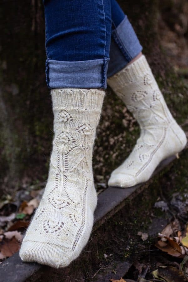 Feet-only view of a woman balancing on a piece of wood, jeans rolled up to show off a pair of knitted socks. The socks are a pale yellow yarn, hand dyed by Cat Tails yarn, with a delicate floral motif by Liz Harris