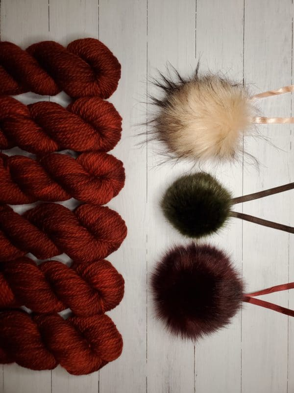 6 skeins of indie dyed yarn in deep red lined up vertically on the left, with three ikigai pom poms on the right