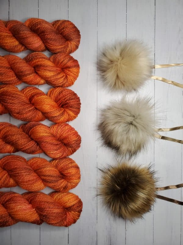 6 skeins of indie dyed yarn in deep brilliant orange with purple lined up vertically on the left, with three ikigai pom poms on the right