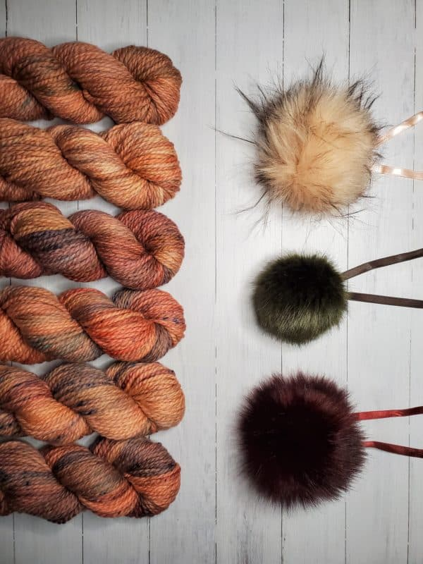 6 skeins of indie dyed yarn in variegated pinkish brown with purple lined up vertically on the left, with three ikigai pom poms on the right