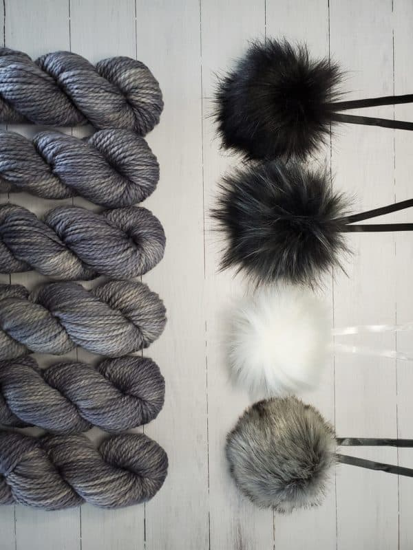 6 skeins of indie dyed yarn in grey lined up vertically on the left, with four ikigai pom poms on the right