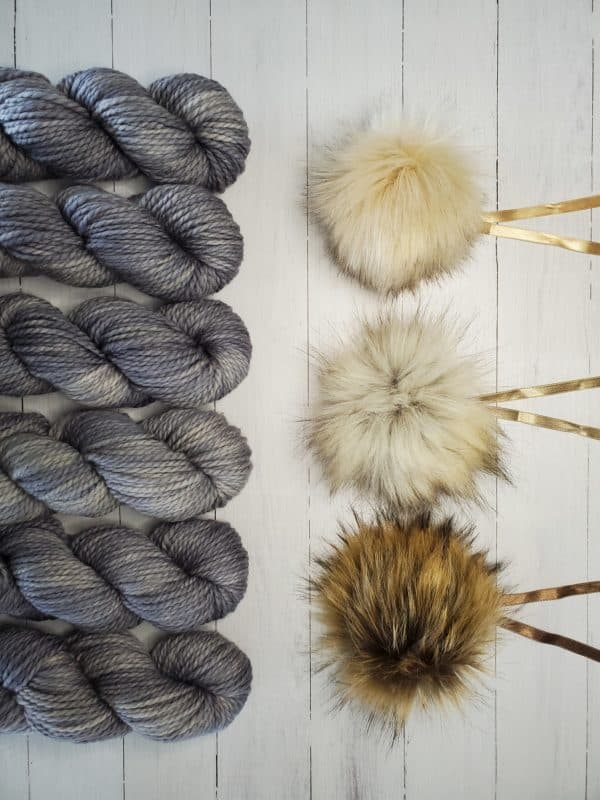 6 skeins of indie dyed yarn in grey lined up vertically on the left, with three ikigai pom poms on the right