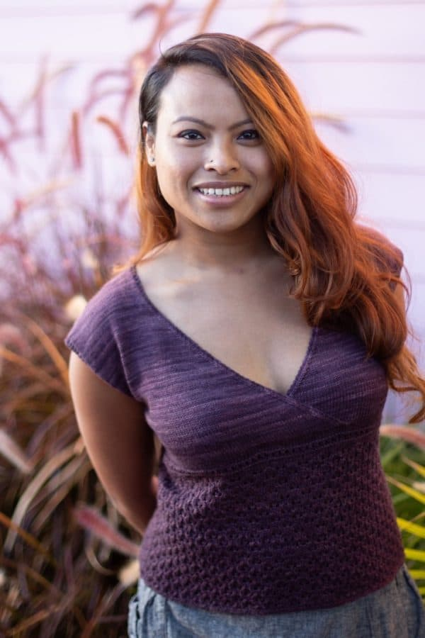 Light brown-skinned woman with flowing hair wearing a v-neck purple capped-sleeve knit sweater.