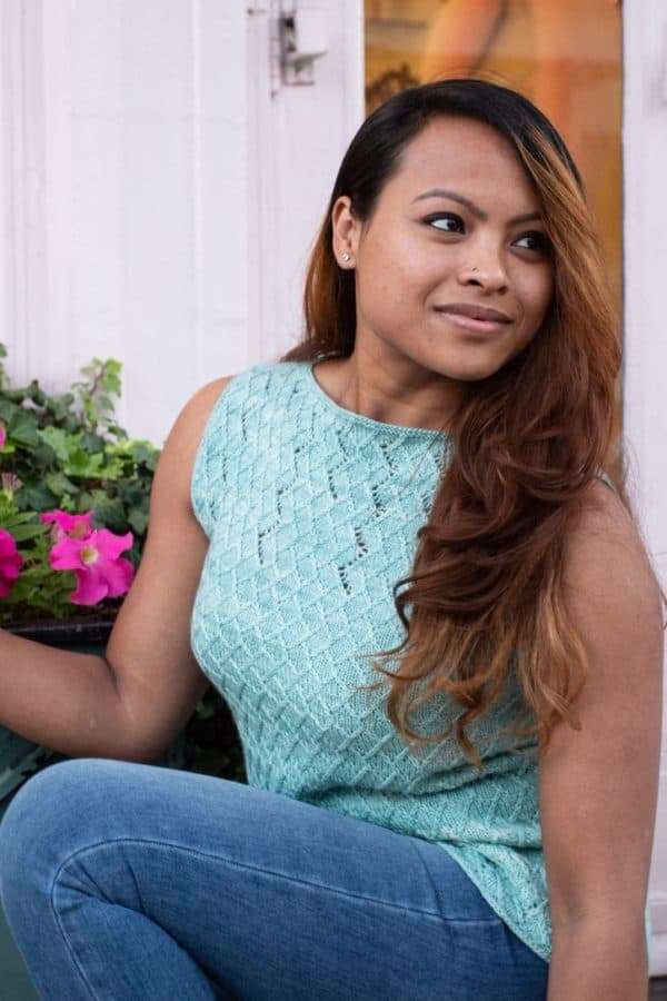 Brown-skinned woman with flowing dark hair crouched by a flower pot and wearing a light green knitted tank with eyelet details