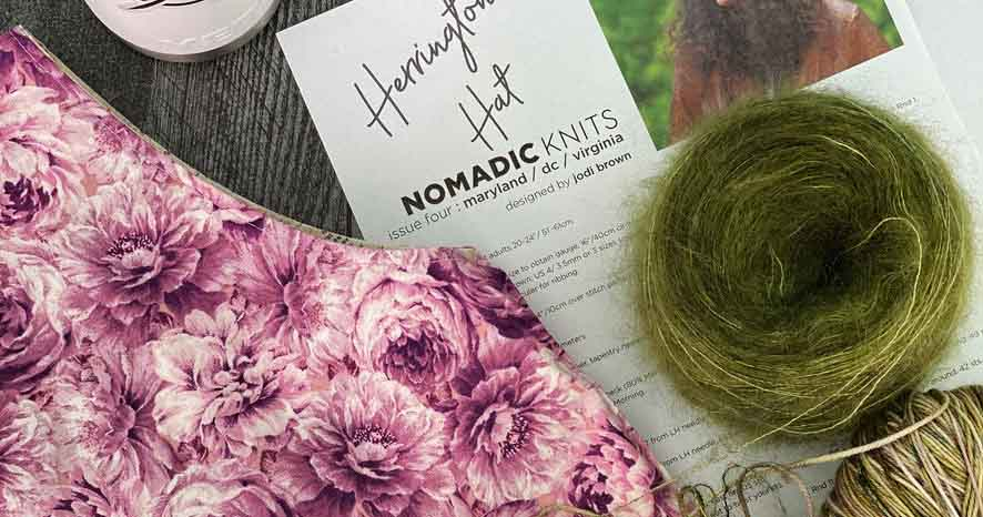 A knitting pattern by Jodi Brown of the Grocery Girls for Nomadic Knits knitting magazine; herrington hat knit with indie dyed yarn and topped with a pom pom