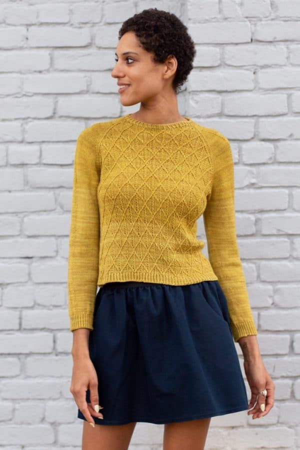 Light skinned Black woman wearing a navy blue skirt and a mustard yellow cabled pullover by Rose Beck