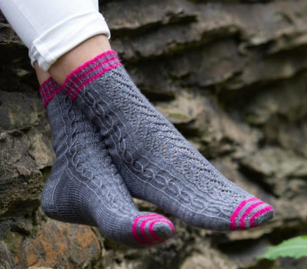 View of a woman's feet. She is wearing Rocky Shores socks, knit in grey and pink. Sock knitting pattern written by Tracie Millar of Grocery Girls knit, in Nomadic Knits creative knitting magazine