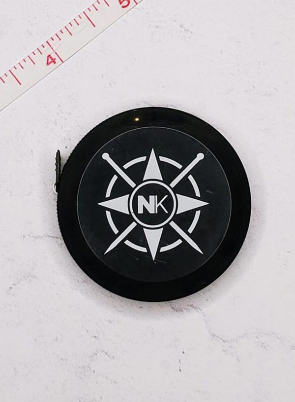 black Nomadic Knits tape measure against a white marble background