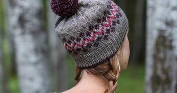 White woman with a blond braid wearing a grey hat with pink and purple Fair Isle and a purple pom pom
