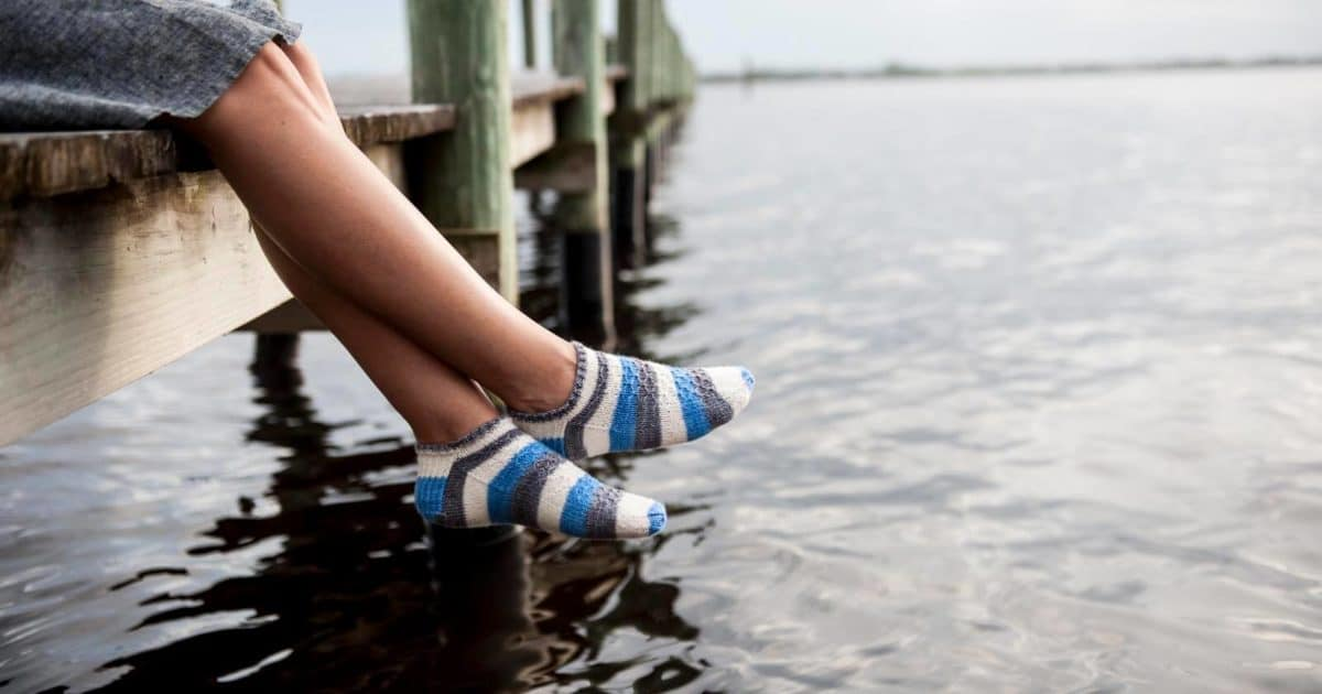 Socks being worn while legs dangle from a water dock