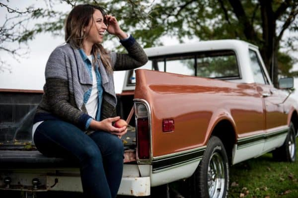 Blond woman sitting on the tailgate of an old brown Ford truck (1970s era). She is wearing jeans, a white tee, and a knitted cardigan. The cardigan is grey, green, and navy, and is a knitting pattern by Melissa Kemmerer using Periwinkle Sheep indie dyed yarn, and can be found in issue two of Nomadic Knits creative knitting magazine.