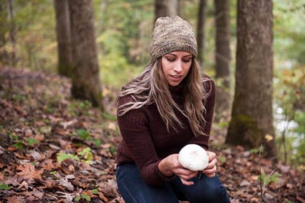 Women wearing knit hat while holding a mushroom outside