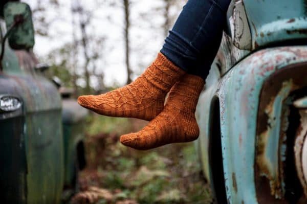 knees-down view of a woman sitting on an old truck; she is wearing burnt orange textured socks over skinny jeans. The knitting pattern is Hell Gate by Deborah Breland, knit using indie dyed yarn from The Periwinkle Sheep