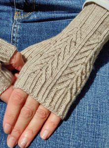 two hands against a denim skirt; hands are wearing mitts knit using pale brownish beige indie dyed yarn from Adelaide Fiber co. Mitts are Mackinac mitts by kate atherley; knitting pattern is available in Nomadic Knits knitting magazine subscription