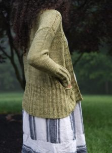 side/back view of Kayla Maressa wearing a pale green cardigan with cable details; Agate Falls was knit with yarn from indie yarn dyer This Craft or That; knitting pattern by Christina Danaee aka Xtina with Wolves, found in Nomadic Knits creative knitting magazine