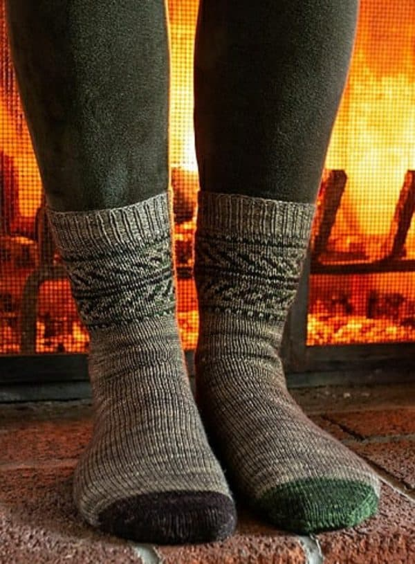 woman standing in front of a lit fireplace wearing green velvet leggings and Killington Socks by Alicia Plummer, knit using Round Mountain Fiber; socks are a Fair Isle knitting pattern.