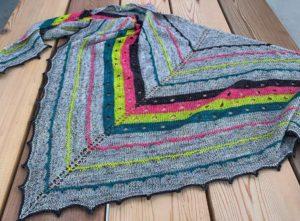 Beautiful triangular shaped shawl in grey and bold stripes (emma's yarn) lying on wooden deck boards.