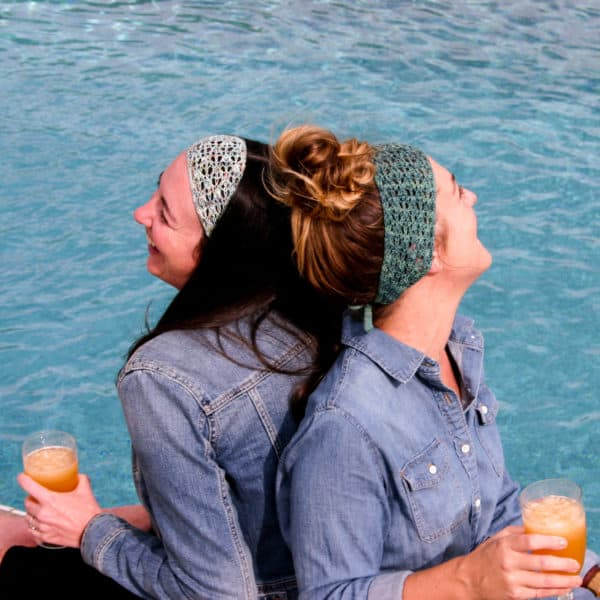 Becky and Melissa sitting back to back poolside enjoying cocktails. Both are wearing denim shirts and Beach Hair Don't Care headbands and laughing. The knitting pattern can be found in issue one of Nomadic Knits creative knitting magazine.