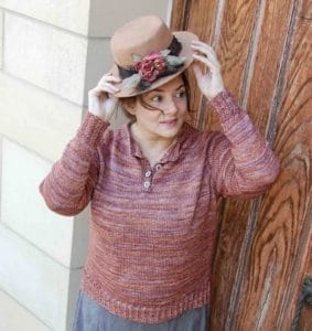 White woman against a wooden fence backdrop wearing a straw hat and a pinkish brown henley sweater; knitting pattern by Melissa Kemmerer using Cabin from indie yarn dyer Driftwood Dyeworks; found in Nomadic Knits creative knitting magazine