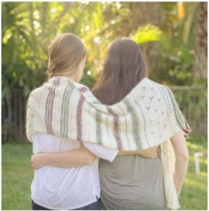 A blond woman (Becky) and a brunette woman (Melissa) from the back with a white, red, and green shawl draped over their shoulders against a background of palm trees