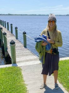 Becky standing in front of a dock over water, dressed in a long skirt, a golden yellow sweater, a knitted hat, and carrying an armload of knitwear.