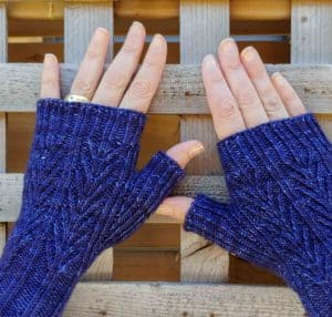 Two hands wearing Mackinac Mitts in indie dyed yarn from Knitterly Things in Blue Blitz; found in Nomadic Knits creative knitting magazine