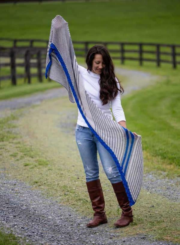 Indie yarn dyer Sandra from Duck Duck Wool wearing a white shirt with blue jeans and brown boots, holding up a biased rectangle shawl in blue, grey, and white. the Blue Ridge shawl is a knitting pattern in Nomadic Knits creative knitting magazine