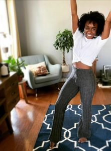 Beautiful Black woman with arms in the air in a joyous pose. She is wearing a white tee knotted at the front, with hand knit grey pants that flatter her beautifully