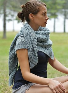 Pretty young white woman from the left side, wearing a ponytail, black tee shirt and a grey hand knitted shawl; knitting pattern by alicia plummer