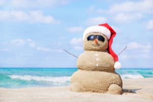 On a beach; a snowman sculpted out of sand, with seashells as buttons, wearing sunglasses and a santa hat, complete with pom pom