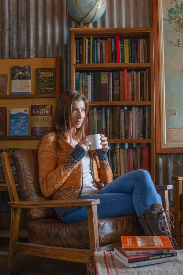 Woman wearing Copper Queen Cardi in book store while drinking from mug