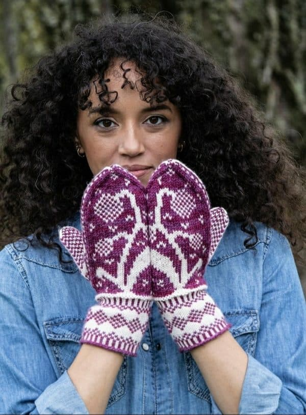 Kayla Maressa wearing a denim shirt and modeling maroon and pale pink mittens with a dandelion motif on the top side of the hands. It is the dandelion mittens knitting pattern by tanis gray knit in yarn from indie yarn dyer little fox yarn