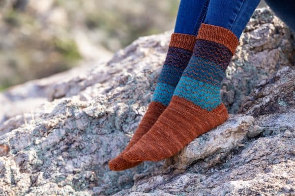 View of two feet wearing Fair Isle socks knit in orange, turquoise, indigo, and navy. Background is a granite rock. Knitting pattern is by Anne Podlesak, knit in indie yarn dyer's wooly wonka fibers; pattern available in Nomadic knits creative knitting magazine