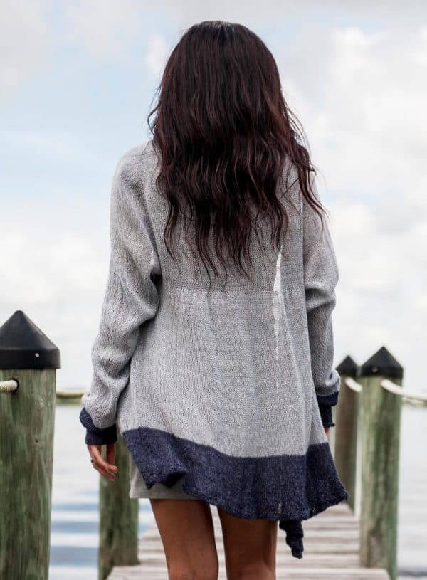 Brunette woman from the back walking along a dock over the water. She is wearing a flowing lacy cardigan that is pale grey/blue with navy trim at the bottom. The knitting pattern was knit with Malabrigo lace yarn and can be found in issue one of Nomadic Knits creative knitting magazine