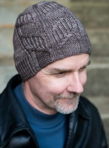 White man with a grey goatee wearing a beautifully cabled grey hand knit hat; knitting pattern by fatimah hinds