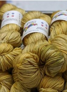 pile of indie dyed yarn from indie yarn dyer up north yarns in michigan; grand sable dunes, a golden yellow color, was used in the third coast cowl and third coast pullover, both by Laura Dobratz of four purls local yarn shop; found in Nomadic Knits knitting magazine subscription