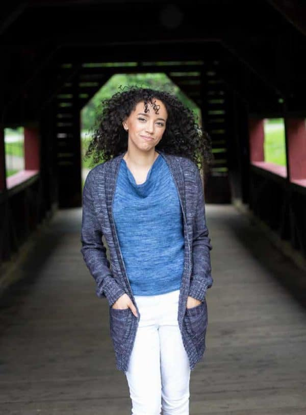 Kayla Maressa modeling two sweaters: Great Falls, a light blue drapey knit tank, under a navy blue open cardigan (Annapolis), both knitting patterns in Nomadic Knits creative knitting magazine. The sweaters are knit in yarn from the indie yarn dyers Dragonfly Fibers and Havirland.