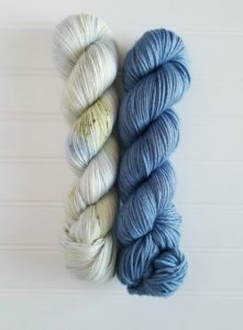 Two twisted hanks of yarn; pale blue speckled on the left and cerulean blue on the right; yarn is from indie yarn dyer Hawari Bazaar of Michigan; colorways used in Dearborn Cardigan and Mile Road Tank, two knitting patterns by Tina Tse; available in Nomadic Knits knitting magazine subscription