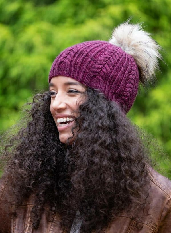 Kayla Maressa modeling a maroon hat with a gray faux fur pom pom; it's the herrington hat by jodi brown of grocery girls knit in blue skin yarn issue four
