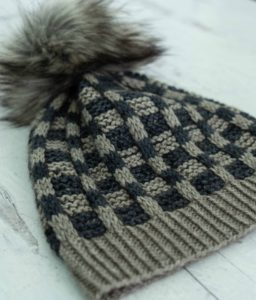 Higgins Lake hat, a grey and navy mosaic pattern with a floofy pom pom, knitting pattern by Jodi Brown of Grocery Girls knit, knit with AJHC indie yarn dyers yarn; found in Nomadic Knits creative knitting magazine