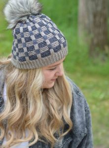 Jodi Brown of Grocery Girls Knit's daughter modeling a blue and grey mosaic patterned hat with a grey faux fur pom pom; indie yarn dyer AJHC wools, knitting pattern found in Nomadic Knits creativ0e knitting magazine