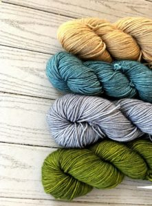 Four twisted hanks of indie dyed yarn, from bottom to top: Moss, Pewter, Ripple, Shoreline; these colorways were used in the Mother of Motors shawl knitting pattern found in Nomadic Knits knitting magazine subscription