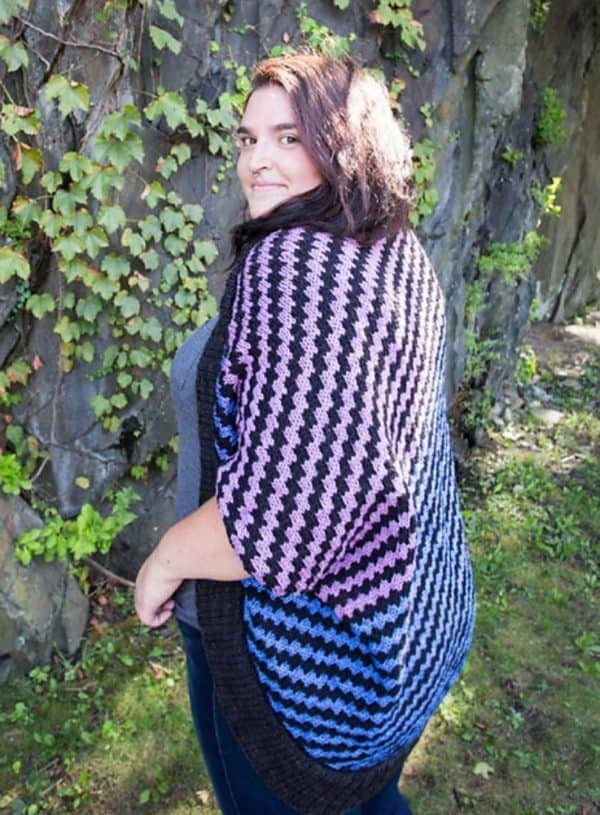Brunette woman from the back, wearing a large cozy shrug knit in Round Mountain Fibers. The pattern is a black, purple and blue mosaic knitting pattern.