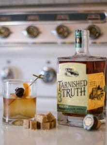 An Old Fashioned cocktail, a bottle of Tarnished Truth Rye Bourbon, brown sugar cubes on a table with an antique cast iron stove in the background