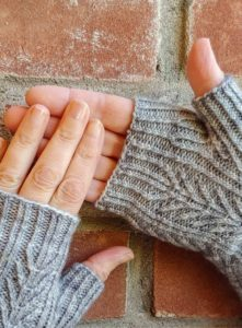 two hands wearing grey fingerless mitts, designed by Kate Atherley and knit using a soft grey from a Michigan indie yarn dyer; pattern available in Nomadic Knits creative knitting magazine