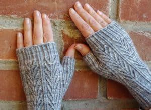 mackinac mitts in grey on a pair of hands with a backdrop of bricks; knitting pattern by Kate atherley in grey yarn from indie yarn dyer; found in Nomadic Knits creative knitting magazine