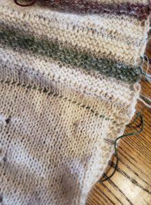 A green yarn lifeline threaded into a white Stockinette stitch background.