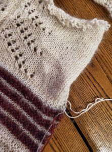 White yarn lifeline threaded into a white wool and mohair Stockinette stitch panel below a pine tree motif.