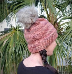Melissa wearing the Lonely Hats Club Hat in bulky pinkish yarn with a grey pompom. She is facing away from the camera and standing in front of a palm tree.